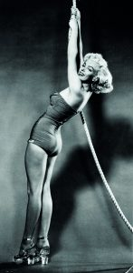 E0MN1W Marilyn Monroe posing in a bathing suit and glass heels